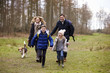 Family walking dog together in the countryside, front view